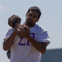 Sigma Pi Alpha Iota Chapter brother carrying dumbbell