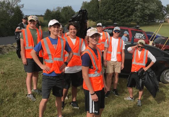 Sigma Pi Alpha Iota Chapter brothers in orange vests