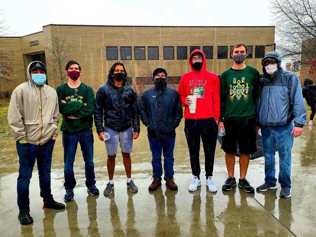 Sigma Pi Alpha Iota Chapter standing in the rain wearking masks