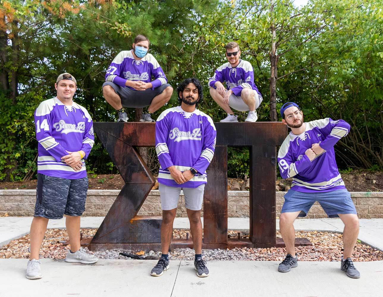 Sigma Pi Alpha Iota Chapter brothers posing around greek letters